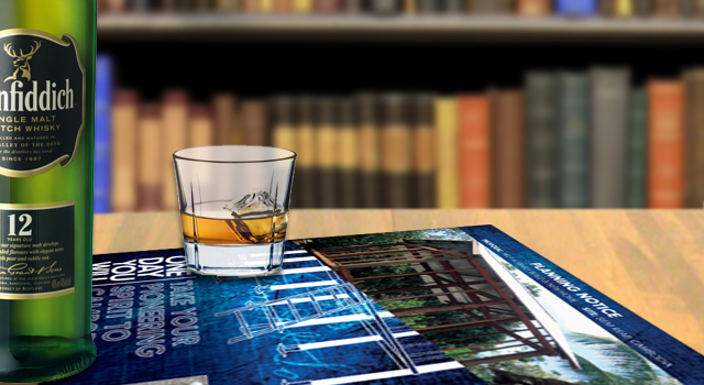 bottle and glass of whiskey in a library